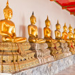 Golden sitting Buddha statue in row - Stock Photo