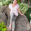 Asian woman smiling on rock in park — Stock Photo