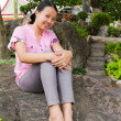 Asian woman smiling on rock in park — Stock Photo #9105508