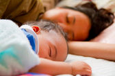 Asian female baby sleeping with her mother — Stock Photo