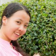 Asian woman smiling in front of tree — Stock Photo #9119473
