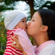 Asian woman kiss her baby — Stock Photo #9211432