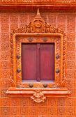 Wooden Thai window on brown tile wall — Stock Photo