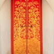 Red wooden door with golden thai pattern — Stock Photo