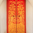 Stock Photo: Red wooden door with golden thai pattern