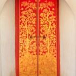 Red wooden door with golden thai pattern — Stock Photo