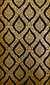 Golden Thai pattern on black wall — Stock Photo