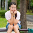 Asian woman sitting and smile on bench — Stock Photo #9936111