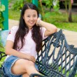 Asian woman sitting and smile on bench — Stock Photo