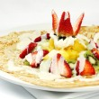 Постер, плакат: French crepes topped with strawberries kiwis and pineapples