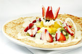 French crepes topped with strawberries kiwis and pineapples — Stock Photo