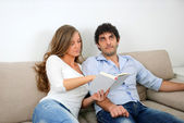 Woman shows her husband interesting part of the book — Stock Photo