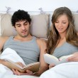 Lying relaxed young couple with a good book — Stock Photo