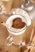 拿铁咖啡加肉桂棒和可可心、 浅景深 — 图库照片