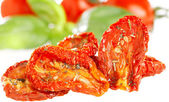 Sun-dried tomatoes with basil leaves and tomato on background, o — Stock Photo