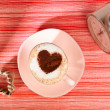 Cappuccino with old alarm clock and heart on red stripy backdrop — Stock Photo