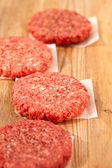 Raw burgers for hamburgers, on wood — Stock Photo