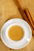 Espresso coffee in thick white cup with Cinnamon sticks , on woo — Stockfoto