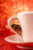 Festive cup of hot drink with cinnamon sticks and golden red bg — Stock Photo