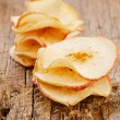 Dried apples slices on old wooden table stacked, shallow dof — Stock Photo #9629792