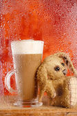 Bunny and coffee latte behind rainy window, shallow dof on glass — Stock Photo