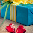 Two red glass hearts with a gift box and flowers — Stock Photo