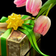 Pink tulips and gift box on black background — Photo