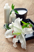 Face/body care concept: lily flower with creams — Stock Photo