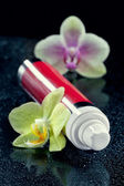 Bottle of face cream/lotion with orchid flowers, closeup shot, o — Stock Photo