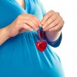 Pregnant woman holding heart over her tummy, closeup shot — Stock Photo #9420578