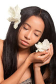 Beautiful young woman with golden tan and flowers in her hair an — Stock Photo