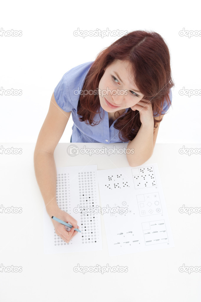 Young woman (student) filling IQ test - intelligence measuring concept. Focused on woman face, top view, white background. — Stock Photo #9514309