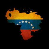 Outline map of Venezuela with grunge flag insert isolated on bla — Stock Photo