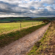 Countryside landscape path leading through fields towards dramat — Stock Photo #8761652