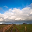 Countryside landscape path leading through fields towards dramat — Stock Photo #8824817