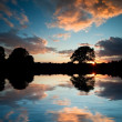 Stunning sunset silhouette reflected in calm lake water — Stock Photo