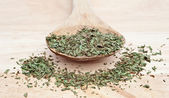 Chopped tarragon on wooden serving spoon with selective focus — Stock Photo