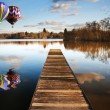 Hot air balloons over sunset lake with jetty — Stock Photo