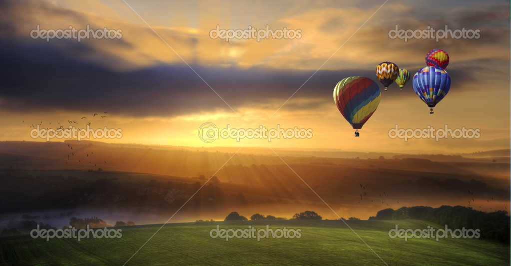 Beautiful golden sunrise glow over fields with hot air balloons flying high — Stock Photo #9505077