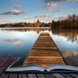 Fishing jetty on lake coing out of magic book pages — Stock Photo