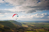 Paragliders over countryside landscape with cloudscape — Stock Photo