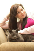 Woman and cat sitting on a sofa — Stock Photo