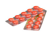 Close up orange capsules and blisters isolated on white — Stock Photo
