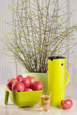 Apples, glass of juice and thermos jug on the table — Stock Photo