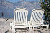 Beautiful lake beach with armchairs — Stock Photo