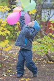 Funny little boy with colorful balloons — Stock Photo