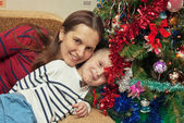 Portrait of mother and son wearing near Christmas tree — Stock Photo