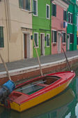 Burano island canal, colored houses and the boat — Stock Photo