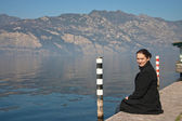 Young woman is sitting on the bank of lake Garda, Italy — Stock Photo