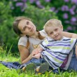 Young mother and her little son having rest in spring park — Stock Photo #9772699